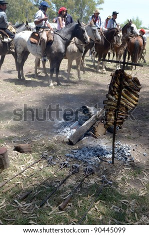 BUENOS AIRES, ARGENTINA - DEC 4: Gauchos riding horses and preparing asado in Gaucho National Day Festival. Dec 4, 2011 in Buenos Aires, Argentina - stock photo