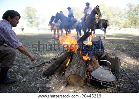 BUENOS AIRES, ARGENTINA - DEC 4: Gauchos riding horses, and preparing fire for asado and mate in Gaucho National Day Festival. Dec 4, 2011 in Buenos Aires, Argentina - stock photo