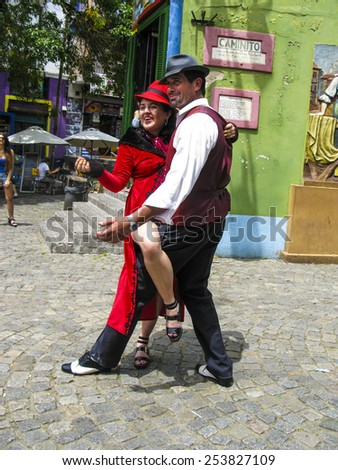 BUENOS AIRES, ARGENTINA - JAN 26, 2015: tango dancer pose for tourists in Caminito Street, Buenos Aires, Argentina. Caminito is a traditional alley, located in La Boca. - stock photo