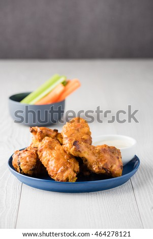 Buffalo chicken wings coated with cayenne pepper sauce and blue cheese dipping