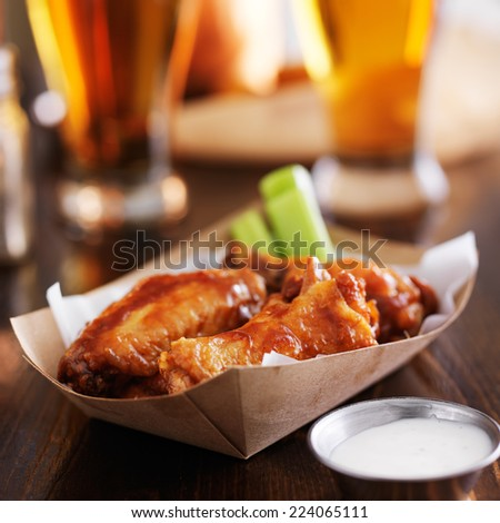 buffalo chicken wings in disposable tray with celery, ranch, and beer - stock photo