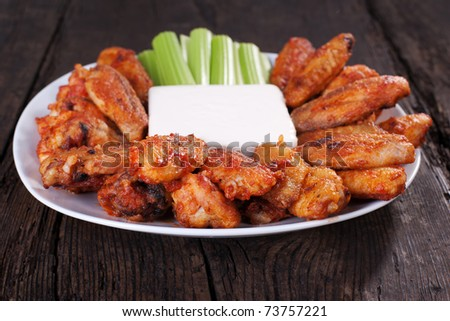Buffalo chicken wings on plate with blue cheese sauce and celery. - stock photo