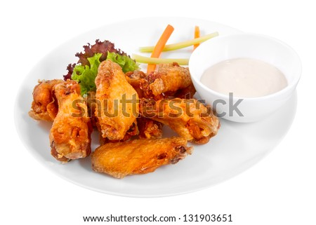 Buffalo chicken wings on plate with sauce, carrots, and celery - stock photo
