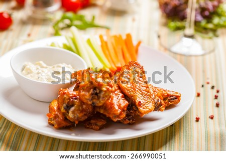 Buffalo chicken wings on plate with sauce, carrots and celery - stock photo