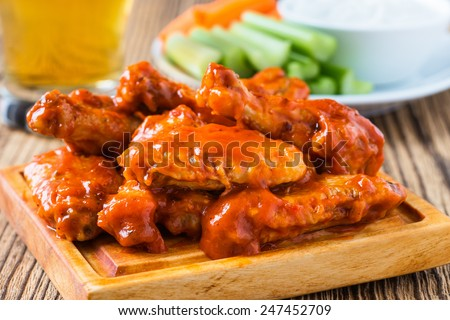Buffalo chicken wings with cayenne pepper  sauce served hot with celery sticks and carrot sticks with blue cheese dressing for dipping and beer - stock photo