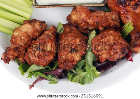 Buffalo Chicken Wings with Celery and Blue Cheese Dressing and Lettuce on a White Plate isolated on white with room for your text. Buffalo Wings are enjoyed by millions of people around the world. - stock photo