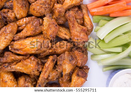 Buffalo chicken wings with celery sticks, carrot sticks and sauce.