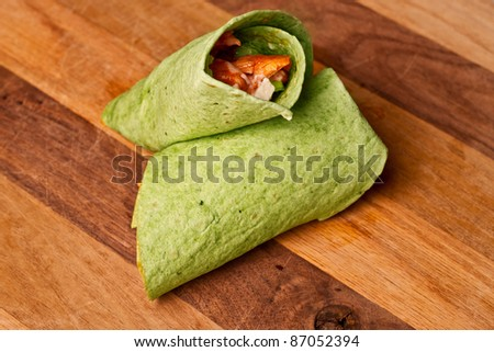 Buffalo chicken wrap in spinach tortilla on wooden surface - stock photo