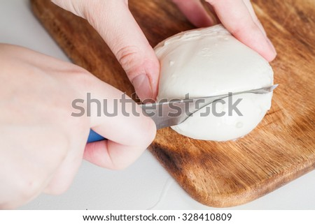 Buffalo mozzarella. Cutting board. Wooden cutting board.