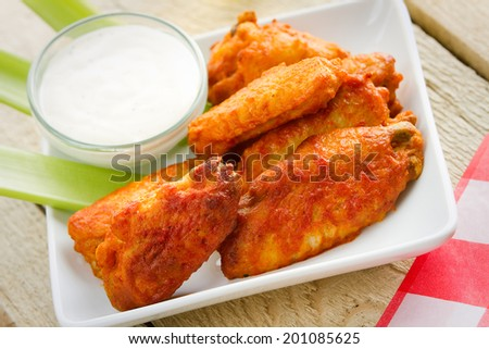 Buffalo Wings - This is a shot of spicy buffalo chicken wings sitting on a plate with ranch dressing and celery.  - stock photo