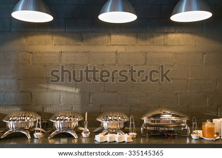 Buffet line food containers shaped shells, with three lighting and dark bricks wall background. - stock photo