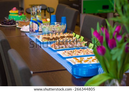 Buffet party table with assortment of different appetizers - mini burgers, rolls, pastry, cookies, salad - stock photo