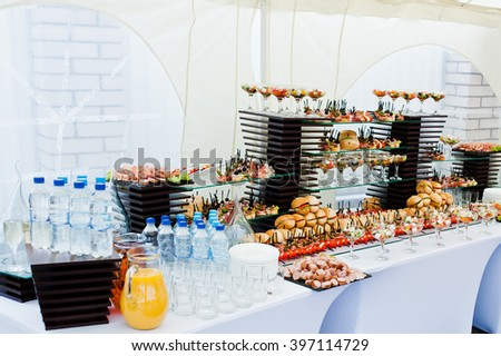 Buffet table of reception with burgers, cold snacks, meat and salads - stock photo