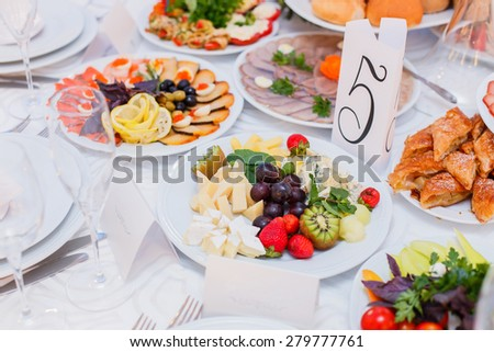 Buffet table served with tasty meals. Cheese platter garnished with fresh strawberries, kiwi, grapes and mint - stock photo