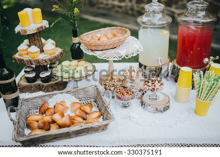 buffet table with refreshments stands on a green glade in the forest, in the area of the wedding banquet - stock photo