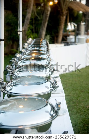 Buffet Table with Row of Food Service Steam Pans - stock photo