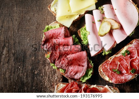 Buffet with assorted open sandwiches displayed at a restaurant with gouda cheese, rare roast beef, ham, mortadella and salami on a rustic wooden table with copyspace - stock photo