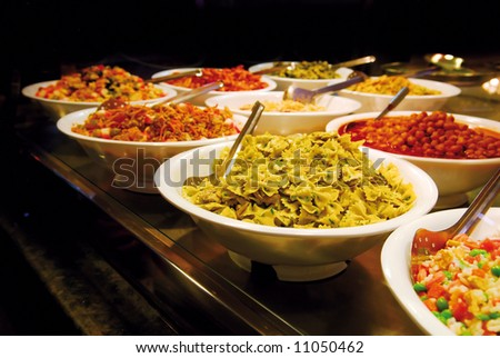 Buffet with butterfly shaped pasta, vegetables, meat, seafood salads on Boqueria market in Barcelona - stock photo