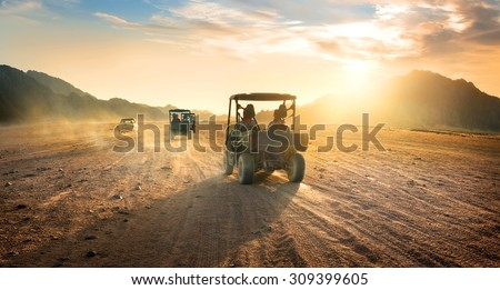 Buggies in sand desert at the sunset - stock photo