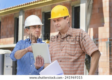 Buiders looking at a tablet computer - stock photo