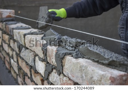 Build a brick wall, bricklaying spreading a bed joint. Bricklaying foundation walls, spread a mortar bed joint for building brick. Brick mason laying old brick. - stock photo