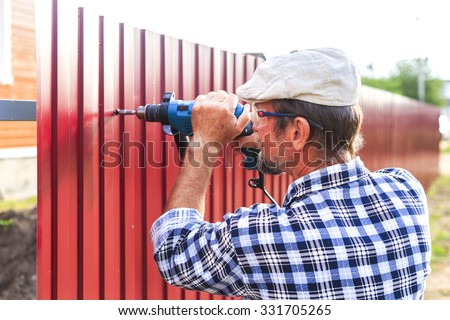 build a metal fence. an elderly man with a drill builds metal fence - stock photo