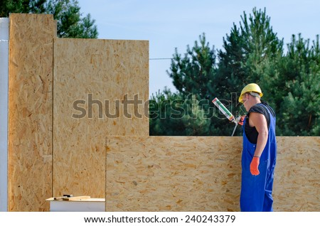 Builder applying glue to an insulated wooden wall panel on a building site for a new build house - stock photo