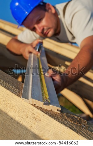 Builder carpenter measuring wood planck looking closely - shallow depth, focus on foreground - stock photo
