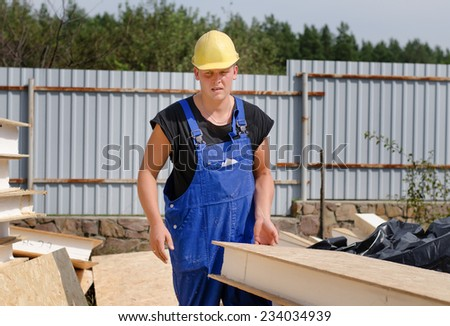 Builder carrying an insulated wooden wall panel on an outdoor bulding site which he has just selected from a pile of building material - stock photo