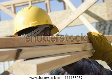 Builder carrying materials at a construction site - stock photo