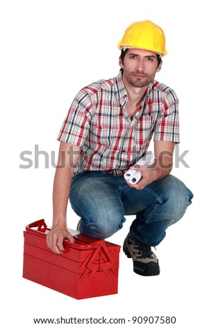 Builder carrying plans and a toolbox - stock photo