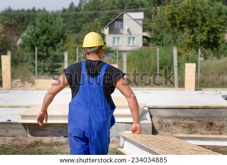 Builder carrying wall insulation on a building site walking away from the camera in his hardhat and overalls - stock photo