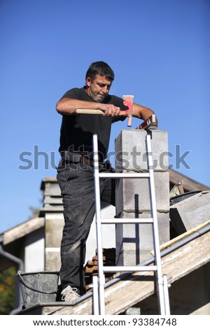 Builder constructing a chimney - stock photo