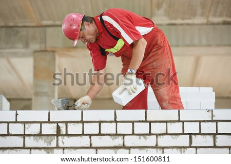 Builder construction mason worker bricklayer installing red brick with trowel putty knife outdoors - stock photo
