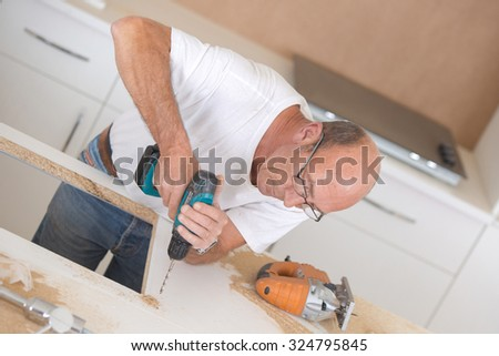 Builder drilling hole in worktop - stock photo