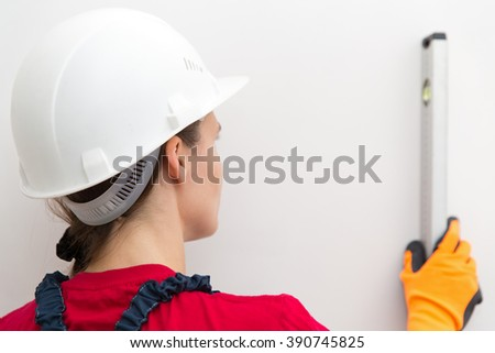 Builder female worker measuring level of wall construction with special tool - stock photo