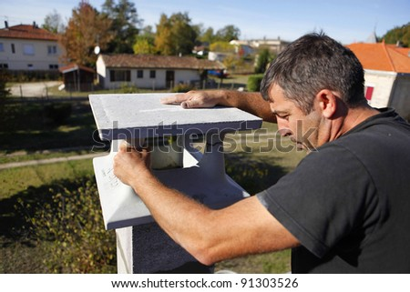 Builder finishing a gatepost - stock photo
