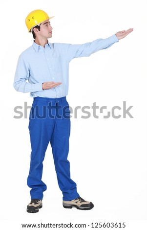Builder gesturing into distance - stock photo