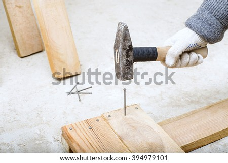 builder hammers a nail with a hammer, a hand in the construction glove holding a hammer, nails and boards,