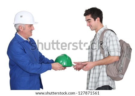 Builder handing hard-hat to young worker - stock photo