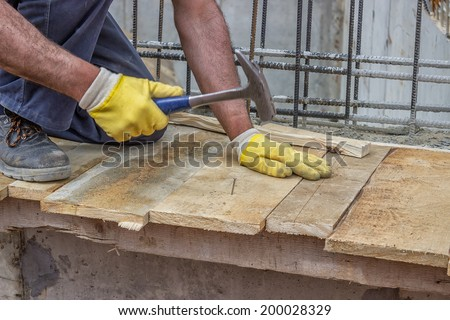 Builder hands hammering a nail into a plank, formwork installation at construction site. Selective focus and motion blur. - stock photo