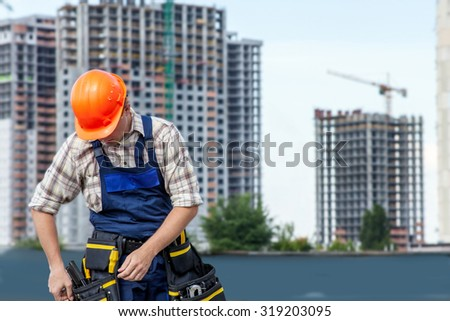 Builder handyman with construction tools. Against the background of a construction site.