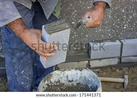 builder holding a brick and with masonry trowel spreading and shaping mortar, at construction site  - stock photo