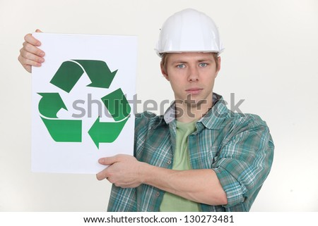 Builder holding recycling symbol - stock photo