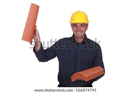 Builder holding roof tiles - stock photo