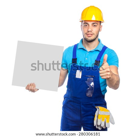Builder holding white board and gesturing thumbs up.  Construction worker with protective hardhat and gloves showing blank banner. Space or copyspace for text. Isolated, studio shot - stock photo