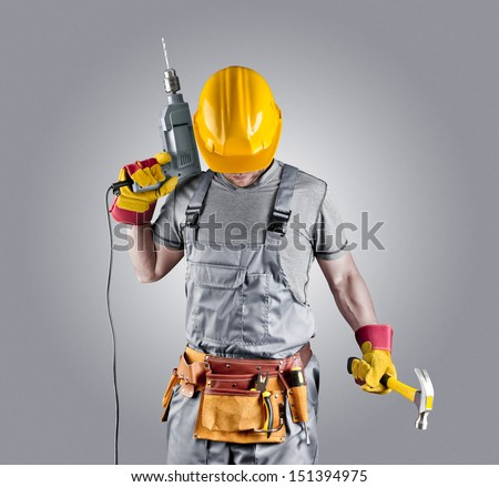 builder in a helmet with a hammer and a drill - stock photo