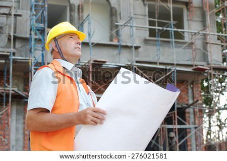 Builder in helmet with a drawing plan photo - stock photo