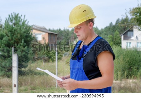 Builder in his hardhat and overalls standing checking paperwork on an urban residential site - stock photo