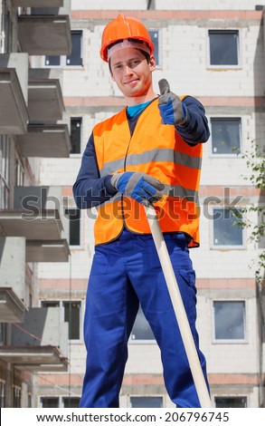 Builder in protective vest and hardhat showing thumbs up sign - stock photo